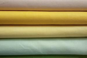 Sklep włókienniczy materiał różne kolory biały żółty zielony